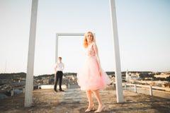 Dana älskvärda härliga par som poserar på taket med stadsbakgrund Ung man och sinnligt blont utomhus- livsstil Royaltyfri Fotografi