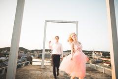 Dana älskvärda härliga par som poserar på taket med stadsbakgrund Ung man och sinnligt blont utomhus- livsstil Arkivbild