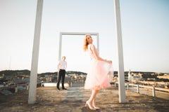 Dana älskvärda härliga par som poserar på taket med stadsbakgrund Ung man och sinnligt blont utomhus- livsstil Royaltyfri Bild