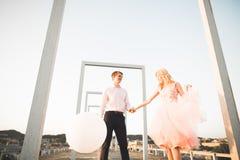 Dana älskvärda härliga par som poserar på taket med stadsbakgrund Ung man och sinnligt blont utomhus- livsstil Arkivfoto