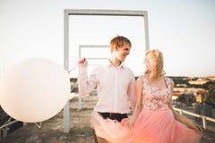 Dana älskvärda härliga par som poserar på taket med stadsbakgrund Ung man och sinnligt blont utomhus- livsstil Arkivbilder
