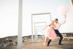 Dana älskvärda härliga par som poserar på taket med stadsbakgrund Ung man och sinnligt blont utomhus- livsstil Fotografering för Bildbyråer