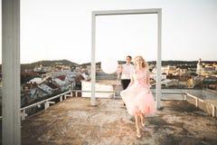 Dana älskvärda härliga par som poserar på taket med stadsbakgrund Ung man och sinnligt blont utomhus- livsstil Arkivfoton