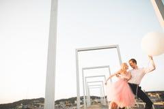 Dana älskvärda härliga par som poserar på taket med stadsbakgrund Ung man och sinnligt blont utomhus- livsstil Royaltyfria Bilder