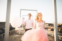 Dana älskvärda härliga par som poserar på taket med stadsbakgrund Ung man och sinnligt blont utomhus- livsstil Royaltyfria Foton