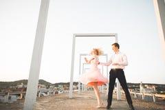 Dana älskvärda härliga par som poserar på taket med stadsbakgrund Ung man och sinnligt blont utomhus- livsstil Royaltyfri Foto