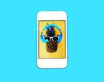 Dana ananas på skärmsmartphonen över färgrika blått royaltyfri bild