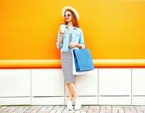 Dana att le kvinnan med en kaffekopp, shoppingpåsar som bär en sugrörhatt Arkivfoton