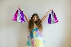 Dana att le lilla flickan med shoppingpåsar och gåvor Arkivbild