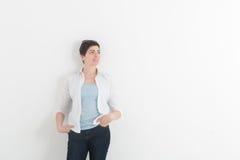 Dana bärande mörker för den unga kvinnan - jeans och den vita skjortan med solglasögon på hennes huvud som ser upp, ler och drömm Arkivfoton