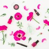 Dana bloggerskrivbordet med skönhetsmedel - läppstift, ögonskuggor, spikar polermedel, och rosa färgen blommar på vit bakgrund Le Arkivfoton