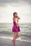 Dana blondinen på strandhavssidan som poserar skon-mindre i vatten royaltyfria foton