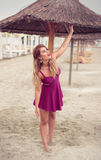 Dana blont lyckligt på havet som poserar skon-mindre på sand fotografering för bildbyråer