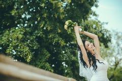 Dana brudflickan i ursnygg bröllopsklänning med bröllopbuketten av blommor fotografering för bildbyråer