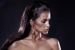 Dana brunetten. Stående av den härliga kvinnan som ha på sig örhängen. Arkivfoto