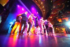 Dança da multidão dos povos em um estágio iluminado Fotos de Stock Royalty Free