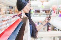 Dana den asiatiska kvinnan med påsen genom att använda mobiltelefonen, köpcentrum Royaltyfri Foto