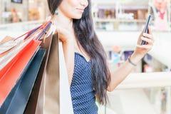 Dana den asiatiska kvinnan med påsen genom att använda mobiltelefonen, köpcentrum Royaltyfri Fotografi
