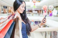 Dana den asiatiska kvinnan med påsen genom att använda mobiltelefonen, köpcentrum Royaltyfri Bild