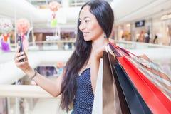 Dana den asiatiska kvinnan med påsen genom att använda mobiltelefonen, köpcentrum Arkivfoton