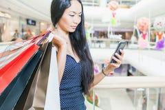 Dana den asiatiska kvinnan med påsen genom att använda mobiltelefonen, köpcentrum Arkivfoto
