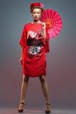 Dana den asiatiska kvinnan som bär den traditionella japanska röda kimonot Fotografering för Bildbyråer