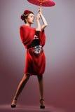 Dana den asiatiska kvinnan som bär den traditionella japanska röda kimonot Royaltyfri Fotografi