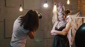Dana den attraktiva modellen för fotoet som i kulisserna - poserar för fotograf lager videofilmer