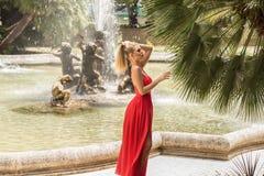 Dana den blonda kvinnan i den röda maxi klänningen som poserar i trädgård royaltyfria bilder