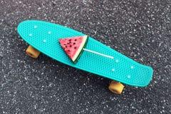 Dana den gröna skateboarden med den nya vattenmelonisglassen på pinnen över texturerad bakgrundstrottoar Arkivfoton
