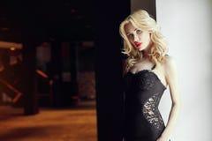 Dana den härliga blonda kvinnan i sexig åtsittande svart klänningstandin Arkivfoto