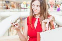 Dana den härliga kvinnan med påsen genom att använda mobiltelefonen, köpcentrum Arkivfoto