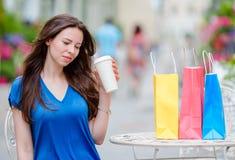 Dana den lyckliga flickan med påsar, når du har shoppat dricka kaffe i openair kafé Sale, consumerism och folkbegrepp royaltyfri fotografi