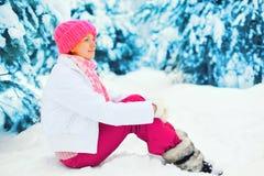 Dana den lyckliga le kvinnan för vintern som sitter nära filialjulträd på snö som bär den färgrika stack hatten i snöig Royaltyfri Foto
