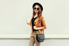 Dana den lyckliga unga le kvinnan med kaffekoppen som bär en retro elegant hatt, solglasögon, bruntomslag och, svärta handväskan Royaltyfri Bild