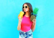 Dana den nätta kalla flickan för ståenden med ananas som dricker fruktsaft från koppen över färgrikt royaltyfri foto