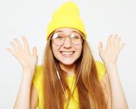 Dana den nätta kalla flickan i hörlurar som lyssnar till musik som bär den gula hatten och t-skjortan över vit bakgrund royaltyfria bilder