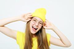 Dana den nätta kalla flickan i hörlurar som lyssnar till musik som bär den gula hatten och t-skjortan över vit bakgrund arkivbild