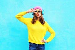 Dana den nätta kalla flickan i hörlurar som lyssnar till musik bärande färgrik rosa solglasögon och tröjan för en hattguling över Arkivbild
