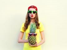 Dana den nätta kalla flickan med ananas över vit Royaltyfria Foton