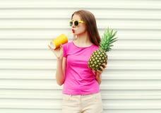 Dana den nätta kalla flickan med ananas som dricker från koppen över vit Royaltyfri Foto