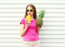 Dana den nätta kalla flickan som dricker från koppen med ananas över vit Royaltyfria Foton