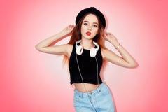 Dana den nätta kalla kvinnan i hörlurar som lyssnar till musik över rosa bakgrund Härlig ung tonårs- flicka med röda kanter, Fotografering för Bildbyråer