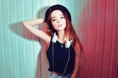 Dana den nätta kalla kvinnan i hatt och hörlurar som lyssnar till musik över rosa bakgrund Härlig ung tonårs- flicka i hatt arkivbilder