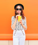 Dana den nätta kvinnamodellen med koppen för fruktsaft för ny frukt som bär vita flåsanden för den svarta hatten över den färgrik Royaltyfri Foto