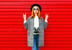 Dana den nätta kvinnan för ståenden med den retro kameran som poserar på ett rött fotografering för bildbyråer