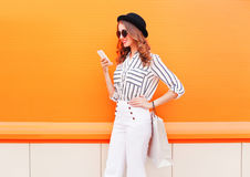 Dana den nätta lyckliga unga le kvinnamodellen genom att använda smartphonen med shoppingpåsar som bär vita flåsanden för en svar fotografering för bildbyråer