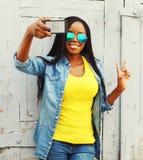 Dana den nätta unga afrikanska kvinnan som tar självporträttfotoet på en smartphone royaltyfri fotografi