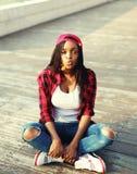Dana den unga afrikanska kvinnan som har gyckel i stad, bärande röd rutig skjorta och baseballmössa royaltyfri fotografi