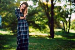Dana den utomhus- ståenden av den ursnygga långa hårkvinnan i lång rutig blåttklänning - fjädra stil Trendig ung flicka i moderik royaltyfri bild